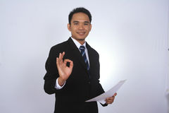 Lycklig ung asiatisk affärsman med papper och uppvisning av det ok tecknet Arkivfoton