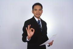 Lycklig ung asiatisk affärsman med papper och uppvisning av det ok tecknet Royaltyfri Foto
