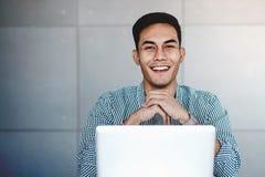 Lycklig ung asiatisk affärsman Working på datorbärbara datorn royaltyfri fotografi