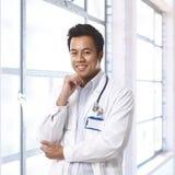 Lycklig ung asiatisk doktor på sjukhuskorridoren Royaltyfri Bild