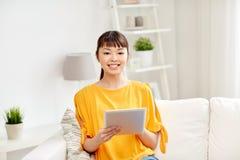 Lycklig ung asiatisk kvinna med minnestavlaPC hemma Fotografering för Bildbyråer