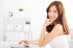 Lycklig ung asiatisk kvinna som använder en bärbar dator Arkivbilder