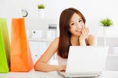 Lycklig ung asiatisk kvinna som använder en bärbar dator med påsar Arkivbild
