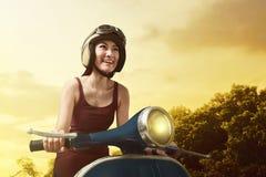 Lycklig ung asiatisk kvinna som kör tappningsparkcykeln royaltyfria bilder
