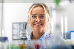 Lycklig ung attraktiv le kvinnaforskare i laboratoriumet Fotografering för Bildbyråer
