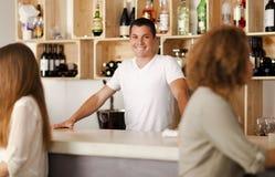 Lycklig ung bartender i en stång Fotografering för Bildbyråer