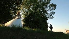 Lycklig ung blond brud i den vita klänningen och brudgummen i dräkten som har gyckel och hoppar nära en gammal medeltida slott arkivfilmer