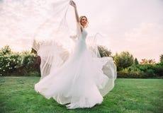 Lycklig ung blond flicka i ett elegant fantastiskt långt vitt bröllopljus och flygklänningaktiviteter och leenden till kameran arkivbilder