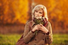 Lycklig ung blond modekvinna som bär klassiskt beige gå för lag som är utomhus- arkivbild