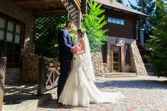 Lycklig ung brud och brudgum i parkera Gifta sig i lantlig stil Trähusby i bakgrunden Är dancien Royaltyfria Foton