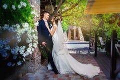 Lycklig ung brud och brudgum i parkera Gifta sig i lantlig stil Trähusby i bakgrunden Är dancien Royaltyfri Fotografi