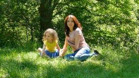 Lycklig ung brunettmoder med den lilla gulliga dottern med blont lockigt hår som utomhus vilar i parkera under soligt arkivfilmer