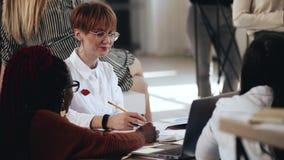 Lycklig ung Caucasian affärskvinna i stilfulla exponeringsglas som möter multietniska partners på det bekväma moderna vindkontore arkivfilmer