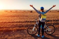 Lycklig ung cyklist som lyfter öppnade armar i höstfältet som beundrar sikten Kvinna som fritt känner sig royaltyfri foto
