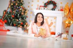 Lycklig ung dam med curluhårgåvor vid spisen nära julgranen nytt år för begrepp arkivfoto