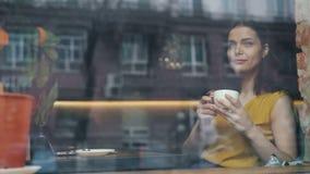 Lycklig ung dam som dricker kaffe som ser ut ur fönstret som sitter i kafé bara lager videofilmer