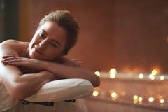 Lycklig ung dam som tycker om på massagetabellen arkivfoton