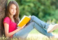 Lycklig ung deltagareflicka med boken royaltyfri foto