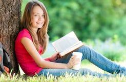 Lycklig ung deltagareflicka med boken Royaltyfri Bild