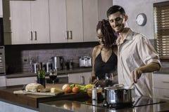 Lycklig ung för parmatlagning för blandat lopp som matställe förbereder mat i köket royaltyfria foton