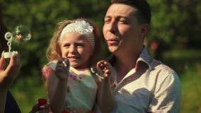 Lycklig ung familj: fader, moder och dotter Modern bubblar, min dotter som spelar med bubblor arkivfilmer