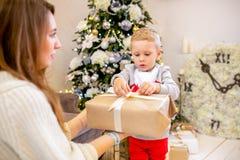 Lycklig ung familj, fader, moder och son, i julafton i hem Öppna gåvor för mamma och för son Nytt års och jultema royaltyfria bilder