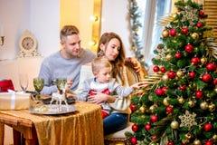 Lycklig ung familj, fader, moder och son, i julafton i hem Dem som sitter på tabellen på julmatställen nytt år arkivfoton