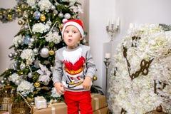 Lycklig ung familj, fader, moder och son, i julafton i hem Lite pojke i jultomten hattställning nära trädet med arkivfoton