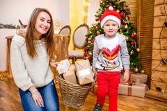 Lycklig ung familj, fader, moder och son, i julafton i hem Mamman och sonen bär en korg med gåvor ` S för nytt år och arkivfoto