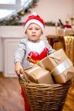 Lycklig ung familj, fader, moder och son, i julafton i hem Pysen bär en korg med gåvor ` S för nytt år och arkivfoto