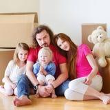 Lycklig ung familj i deras nya hem Fotografering för Bildbyråer