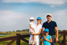 Lycklig ung familj i golfklubbhus Arkivfoto