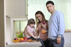 Lycklig ung familj i kök Arkivfoto