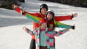 Lycklig ung familj i Ski Suit With Funny Children i ljus vinterkläder Att gå rymma händer parkerar in underbart stock video