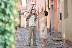 Lycklig ung familj i stadsgata Arkivfoto