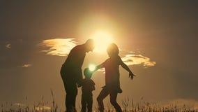 Lycklig ung familj med barn som kör runt om fältet, kontur på solnedgången arkivfilmer