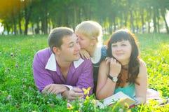 Lycklig ung familj med ett barn som ligger på gräset Royaltyfri Foto