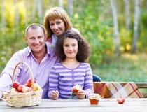 Lycklig ung familj på höstpicknick Arkivfoto