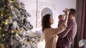 Lycklig ung familj på julgarnering stock video