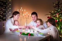 Lycklig ung familj på julmatställen Arkivfoton