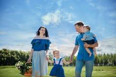 Lycklig ung familj som går ner vägen utanför i grön natur royaltyfria foton