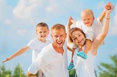 Lycklig ung familj som har gyckel tillsammans Arkivbilder