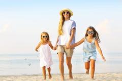 Lycklig ung familj som har rolig spring på stranden på solnedgången familj Royaltyfria Bilder