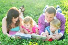 Lycklig ung familj som kopplar av i natur royaltyfria foton