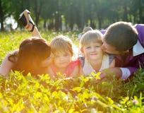 Lycklig ung familj som ligger på gräset fotografering för bildbyråer