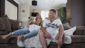 Lycklig ung familj som sitter på sofaen Lycklig familj som tillsammans spenderar tid hemma Två flickor som kramar deras föräldrar arkivfilmer