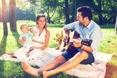 Lycklig ung familj som spenderar utomhus- tid på en sommardag Arkivbild