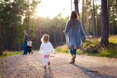 Lycklig ung familj som tar en gå i en parkera, baksidasikt Familj som tillsammans går längs den mest forrest banan med deras dott arkivbilder