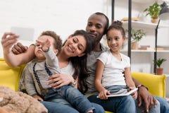 lycklig ung familj som tar selfie på soffan royaltyfri bild