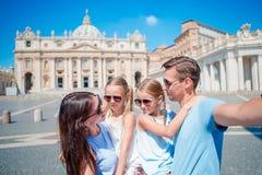 Lycklig ung familj som tar selfie på Sts Peter basilikakyrkan i Vatican City, Rome Lyckliga loppföräldrar och ungar Arkivbild